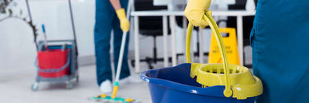 Photo pour Professional office cleaner is holding a bucket - image libre de droit