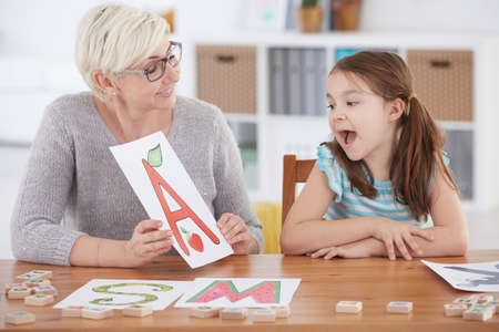 Photo pour Girl with language disorder spelling letters with speech therapist - image libre de droit