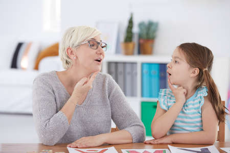 Foto de Stuttering girl and speech therapist doing exercises - Imagen libre de derechos