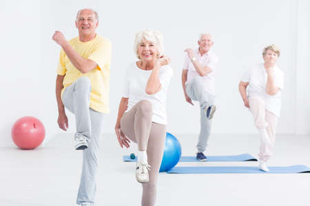 Foto de Group of active seniors exercising at the gym and smiling - Imagen libre de derechos