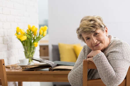 Photo for Smiling senior woman sitting on a chair and old photo album laying on a table behind her - Royalty Free Image