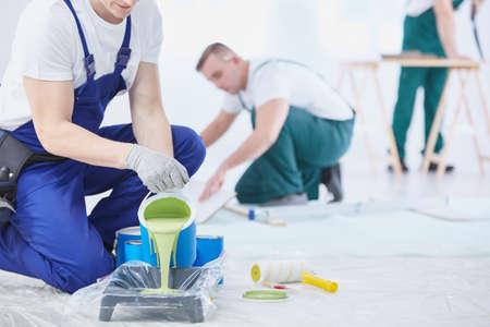 Photo pour Professional interior construction worker pouring green color to paint - image libre de droit