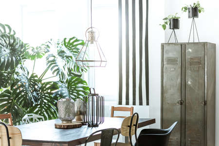 Photo pour White, industrial dining room with metal wardrobe and wood table - image libre de droit