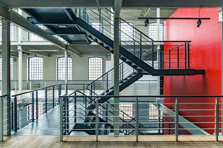 Photo pour Industrial building interior with red wall and black, metal staircase - image libre de droit