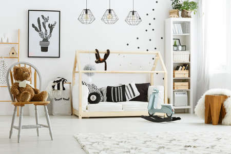 Photo pour White kid bedroom with house bed, lamps, chair and poster - image libre de droit