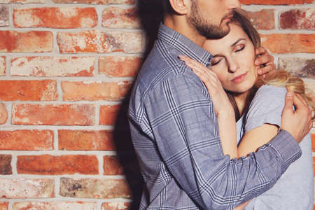 Photo for Handsome man hugging his girlfriend against brick wall - Royalty Free Image