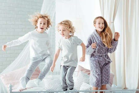 Photo pour Small brothers and sister jumping on bed - image libre de droit