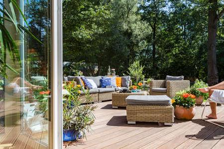 Foto de New style villa terrace with rattan furniture set and decorative flowers - Imagen libre de derechos