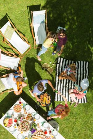 Foto de Top view of group of friends having picnic in garden - Imagen libre de derechos