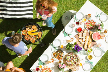 Foto de Man and woman grilling food for party garden, top view - Imagen libre de derechos