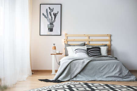 Photo for Black and white bedroom with grey accessories, big window and cactus poster - Royalty Free Image