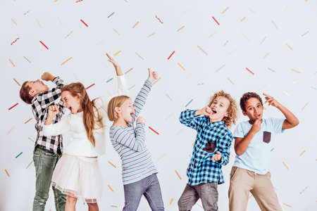Photo for Group of happy boys and girls pretending to sing at a party - Royalty Free Image