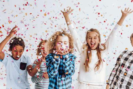 Foto de Happy kids having fun in a room full of confetti - Imagen libre de derechos