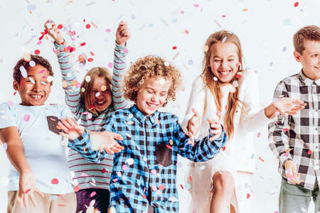 Photo for Happy kids throwing colorful confetti in a room - Royalty Free Image