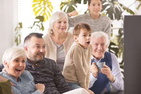 Photo pour Excited family cheering in front of tv - image libre de droit