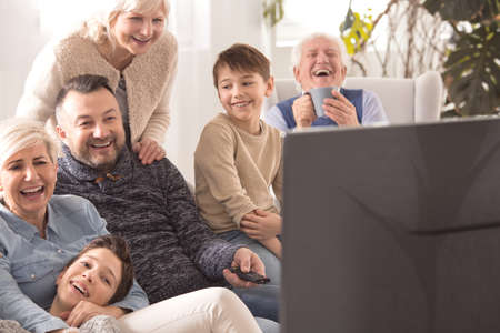 Photo pour Loving multigenerational family laughing while watching television together - image libre de droit