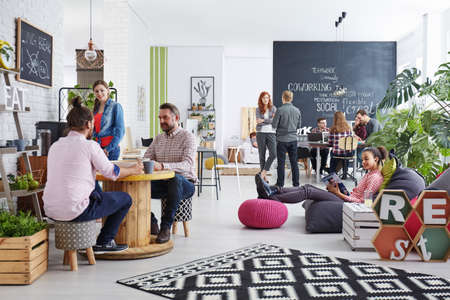 Foto de People working in modern agency relaxing during lunch break - Imagen libre de derechos