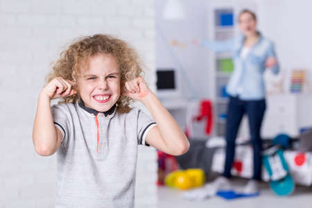 Photo for Rebellious boy covering his ears with mother behind - Royalty Free Image