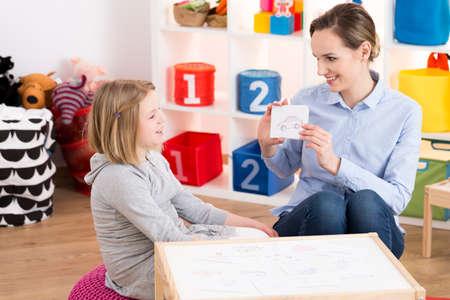 Photo pour Little blond girl visiting professional speech therapist - image libre de droit