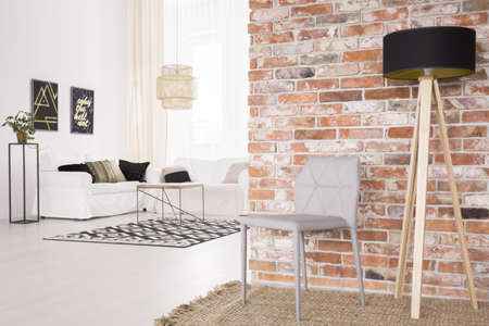 Foto de Grey designer chair and black lamp by the red brick wall - Imagen libre de derechos