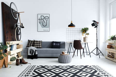 Foto de Hipster style, white living room with sofa, pouf, carpet, bike - Imagen libre de derechos