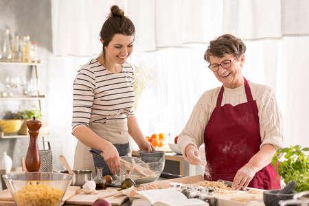 Foto de Happy grandma and granddaughter preparing dinner together - Imagen libre de derechos