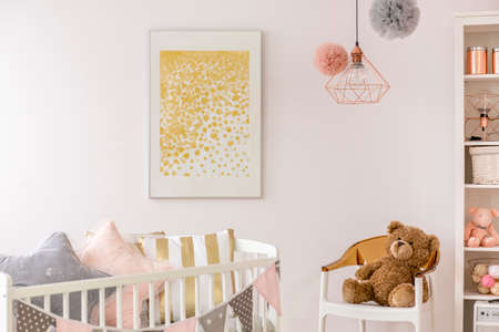 Foto de Toddler bedroom with white crib, poster, chair and teddy bear - Imagen libre de derechos
