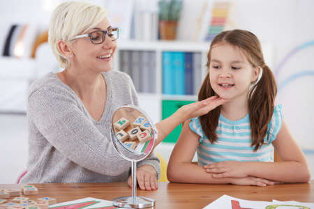 Photo pour Speech therapist touching girl's chin during articulate therapy - image libre de droit