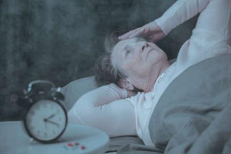 Photo pour Senior woman having sleep disorder, lying in bed - image libre de droit