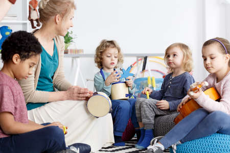 Photo pour Four preschoolers having fun in kindergarten playing the instruments - image libre de droit