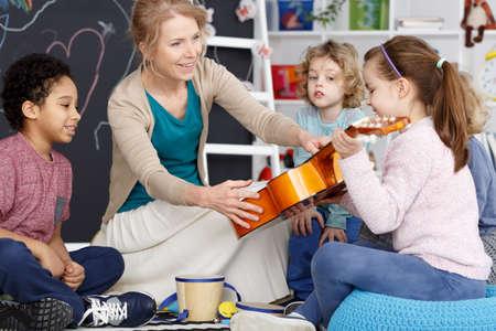 Photo pour Little preschool girl holding teacher's guitar on music lesson - image libre de droit
