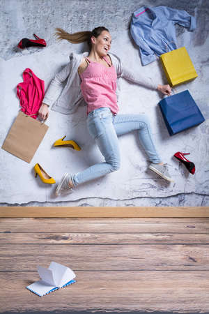 Photo pour Young woman surrounded by new clothes and shoes - image libre de droit