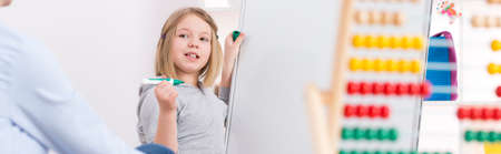 Foto de Girl during extra classes writing on a white board - Imagen libre de derechos