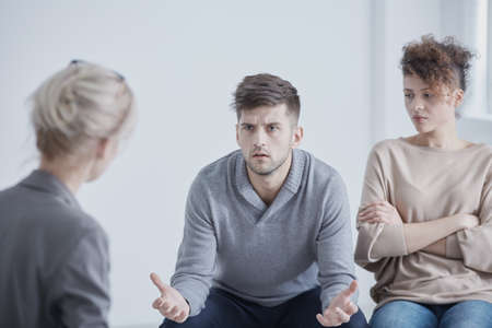 Photo for Angry young man and his sad wife on a marriage therapy - Royalty Free Image