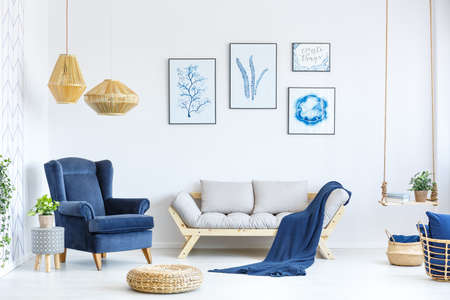 Photo for White and blue living room with sofa, armchair, lamp, posters - Royalty Free Image