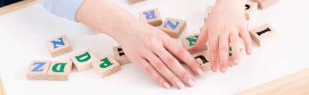 Foto de Close-up of teacher's and girl's hand placing the letters - Imagen libre de derechos