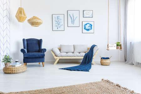 Foto de White home interior with sofa, armchair, posters, lamps and rug - Imagen libre de derechos