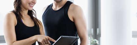 Photo pour Woman planning workout routine with her personal trainer - image libre de droit