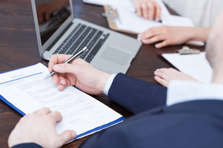 Photo for Members of cadre checking a resume after recruitment review - Royalty Free Image