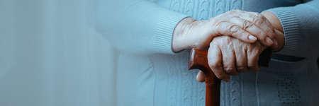 Foto de Close up of senior disabled woman's hands holding walking stick - Imagen libre de derechos