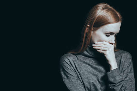 Photo pour Bulimic woman covering her mouth, black background - image libre de droit