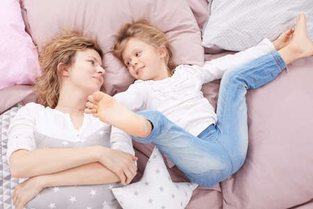 Girl holding her legs while laying in bed with mom