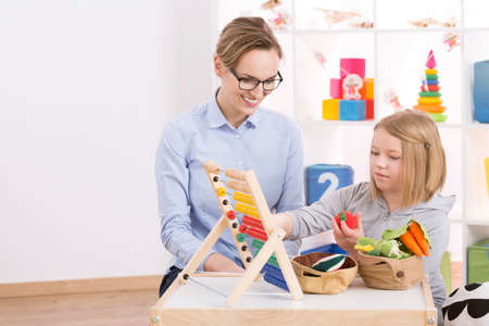 Photo pour Female tutor and little girl counting with abacus in playroom - image libre de droit