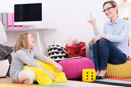 Photo for Psychotherapist woman using play activities for teaching young girl to count - Royalty Free Image