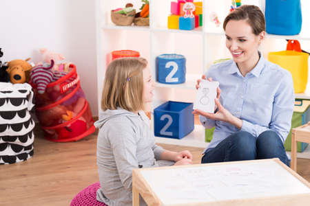 Foto de Child counselor showing drawings to little smart girl with ADHD - Imagen libre de derechos