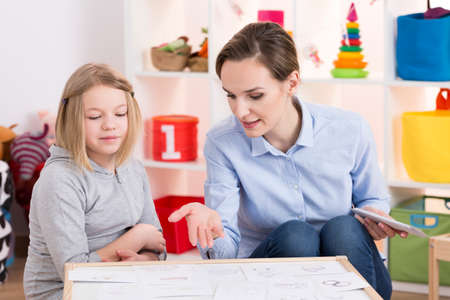 Foto de Young female therapist and little girl during play therapy session - Imagen libre de derechos