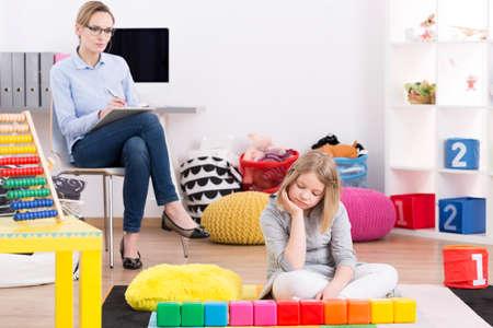 Foto de Female psychologist testing young girl with Asperger's syndrome symptoms - Imagen libre de derechos