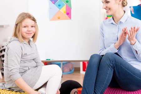 Foto de Female speech therapist smiling at happy little girl making progress - Imagen libre de derechos