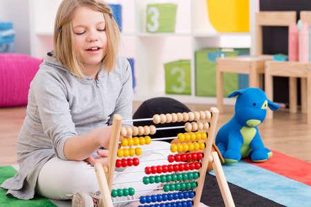 Foto de Smart little genius girl playing with abacus in colorful room - Imagen libre de derechos