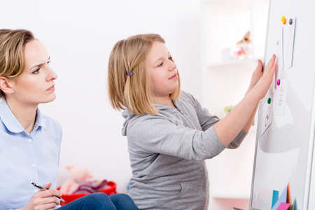 Foto de Psychologist using play therapy for testing child with autism disorder - Imagen libre de derechos